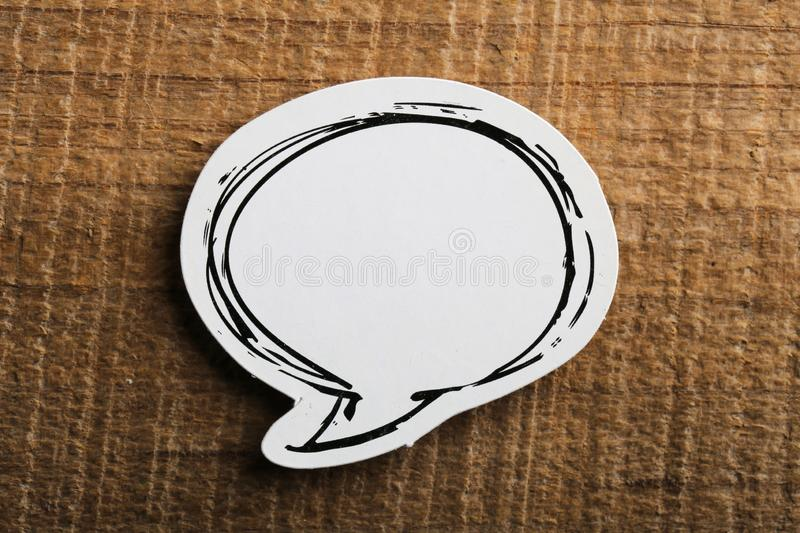Blank White Speech Bubble Paper On Wooden Background royalty free stock photo