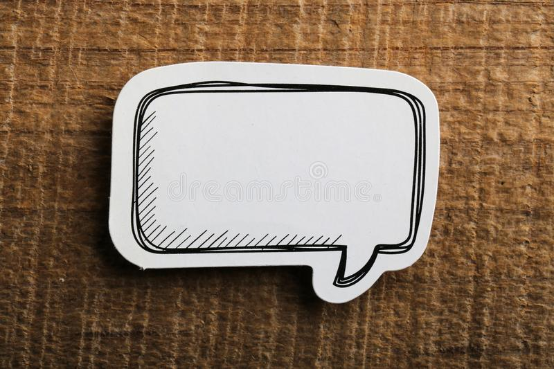 Blank White Speech Bubble Paper On Wooden Background royalty free stock image