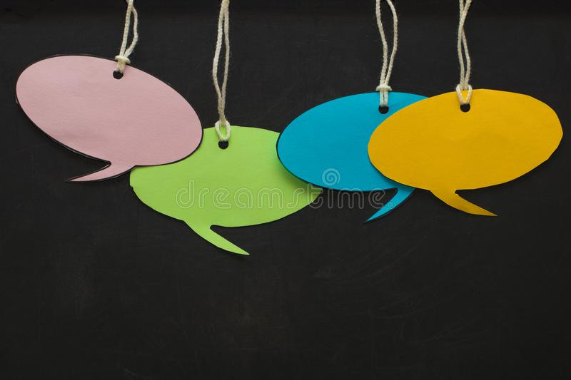 Blank white speech bubbles hanging from a cord in front of a black Board.  royalty free stock photography