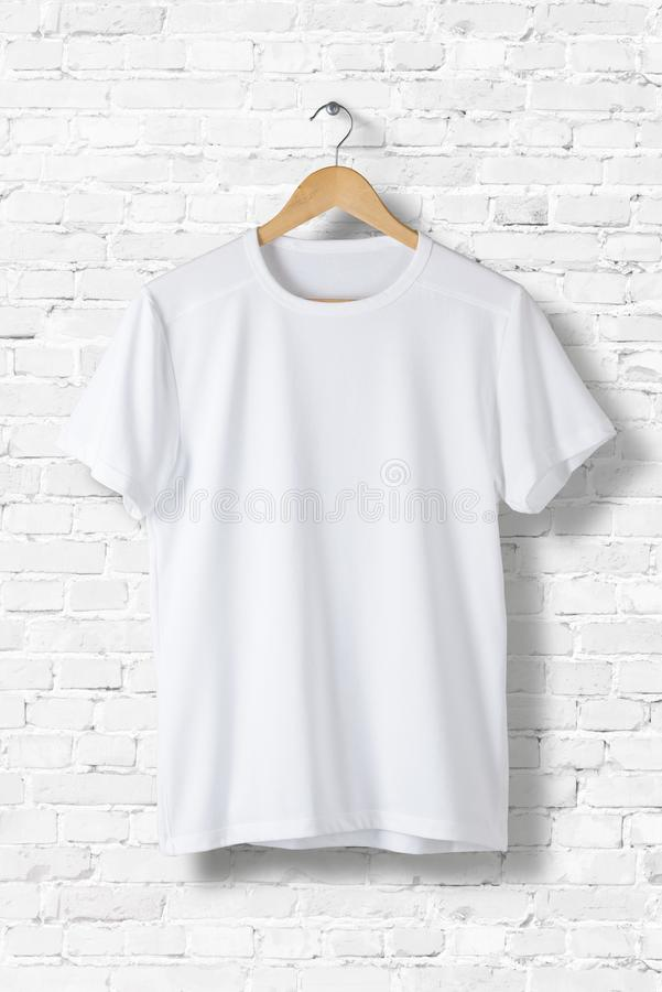 Blank White T-Shirt Mock-up hanging on white wall, front side view. stock image