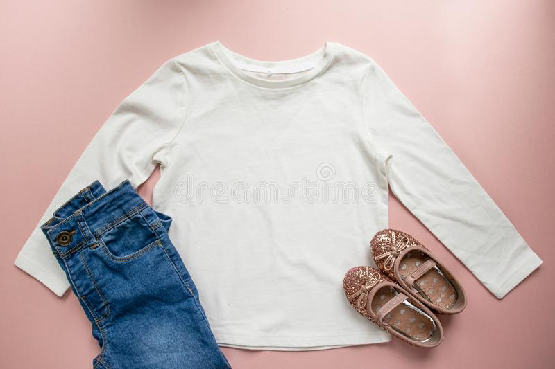 Blank white toddler girl`s long sleeved t-shirt on pink background with rose gold glitter ballet pumps and blue jeans royalty free stock photography