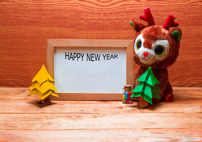Blank whiteboard for your text on wooden background. Blank whiteboard for your text on wooden background with Christmas tree, gift box and Teddy reindeer royalty free stock image