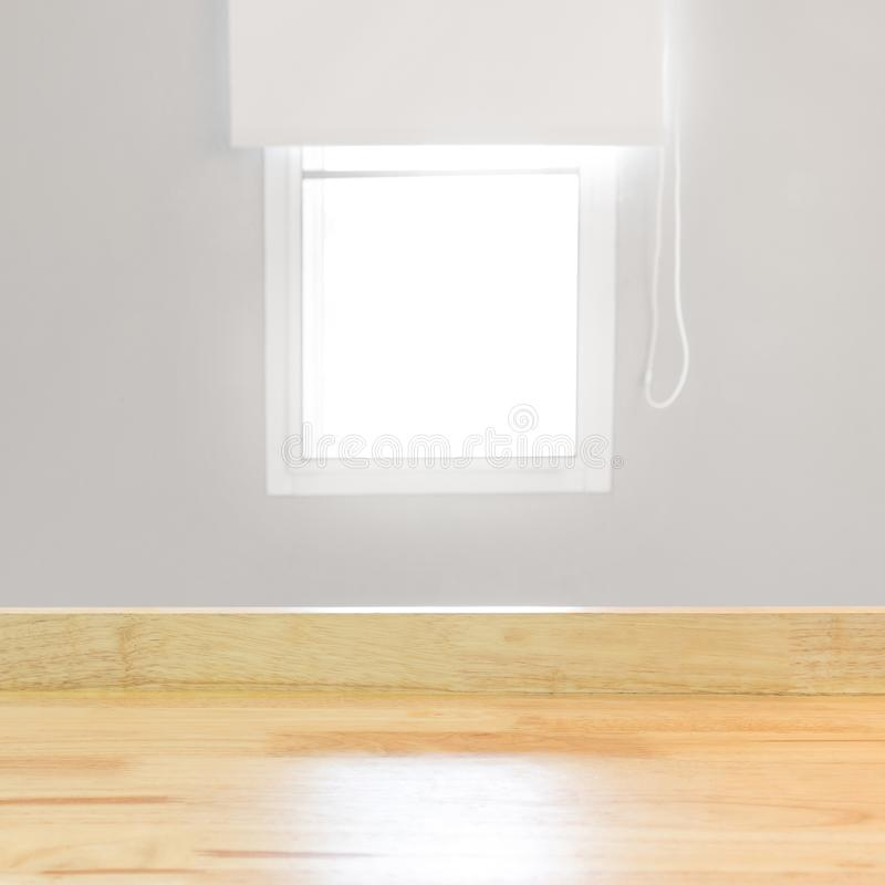 Blank wood table top view and blur window on grey wall from office with sunlight. Modern room for product display or design royalty free stock photos