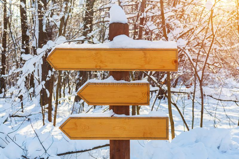 Blank wooden directional arrows on a post, covered by snow royalty free stock photo