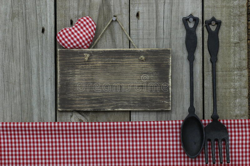 Blank wooden sign with red gingham heart and tablecloth and cast iron spoon and fork. Blank wooden sign with red gingham heart and tablecloth hanging on wood royalty free stock images