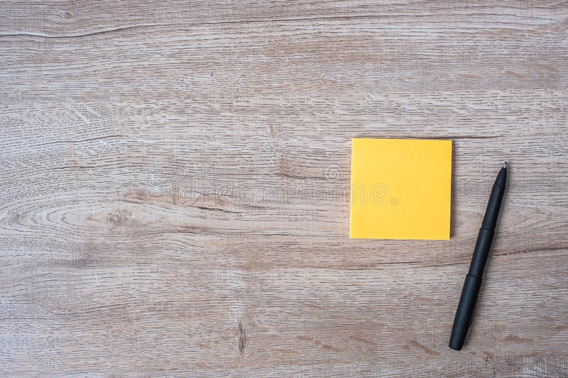 Blank yellow note with pen on wooden table background. Strategy, mission, vision and Goal concept.  stock photos