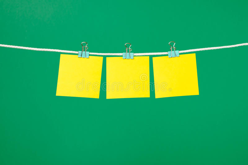 Blank yellow paper sheet on the string. Over green background royalty free stock photography