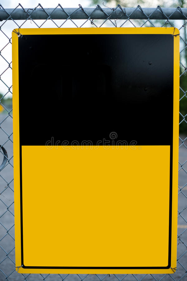 Blank Yellow Sign on Chain-Link Fence stock photo