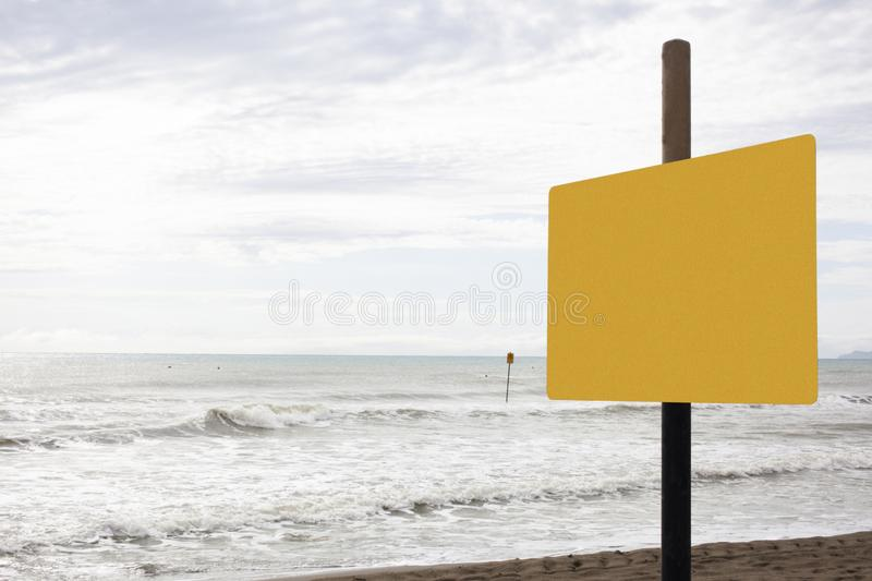 A blank yellow signboard on a beach with space for your text and clipping path for the signboard. A blank yellow signboard on a beach with space for your text royalty free stock images