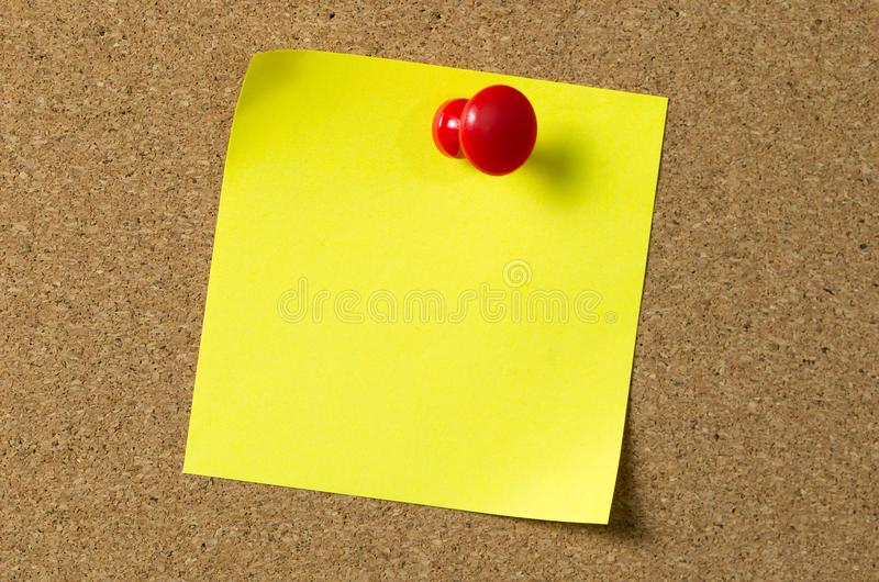 Yellow note pad attached to corkboard royalty free stock photos