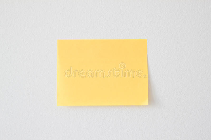 Blank Yellow Sticky Note on the White Wall royalty free stock photos