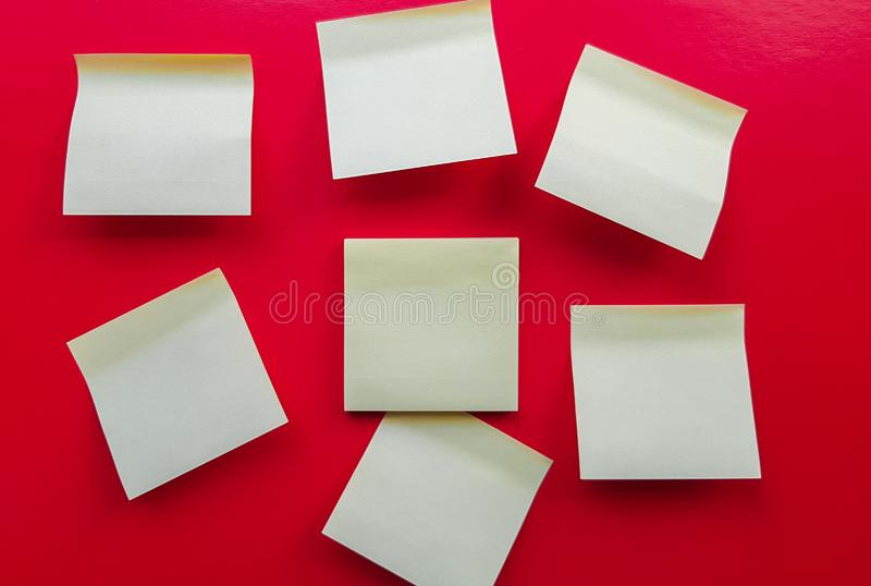 Blank yellow sticky notes on a red background, business work concept. Yellow commemorative stickers on the red wall. Layout royalty free stock images