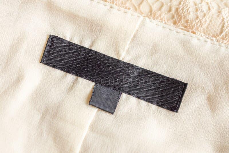 Blanka etiketter för svarta tvättkläder på textilier fotografering för bildbyråer