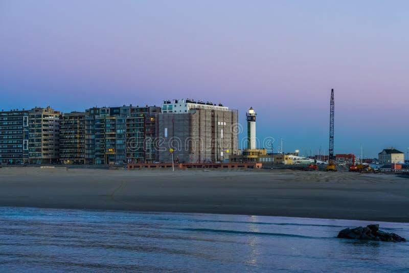 Blankenberge-Strand, Ansicht über die Stadt mit beleuchtetem Leuchtturm, populäre belgische Stadtarchitektur bis zum Nacht lizenzfreie stockbilder
