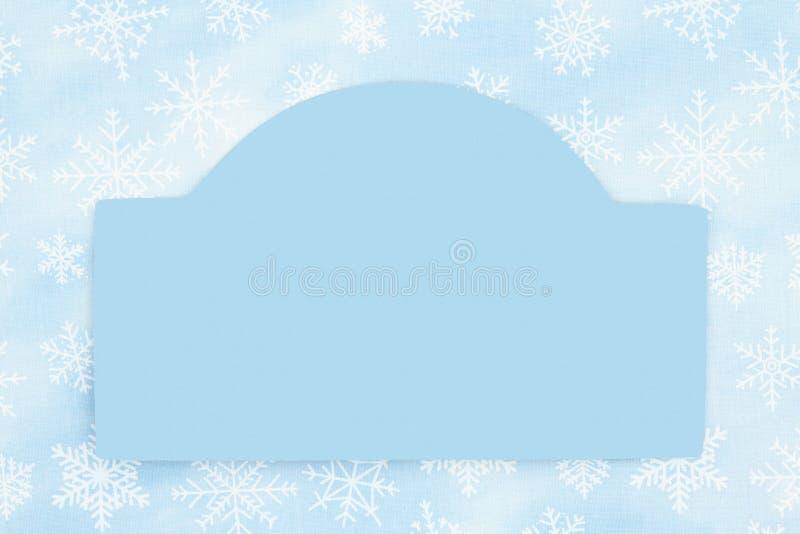 Blankes Holzschild mit blauem Schneeflocken-Hintergrund lizenzfreie stockbilder
