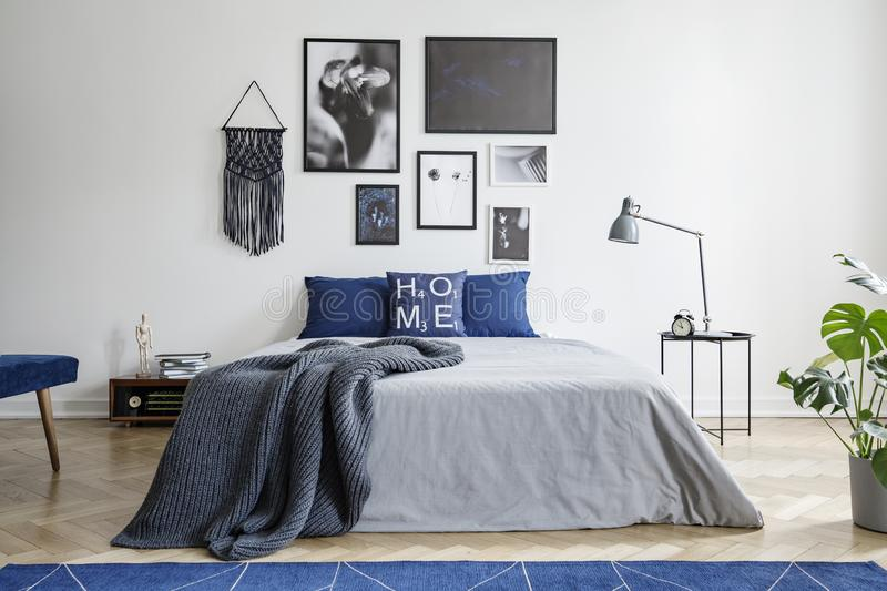 Blanket on bed with blue pillows in white bedroom interior with gallery and lamp on table. Real photo stock photo