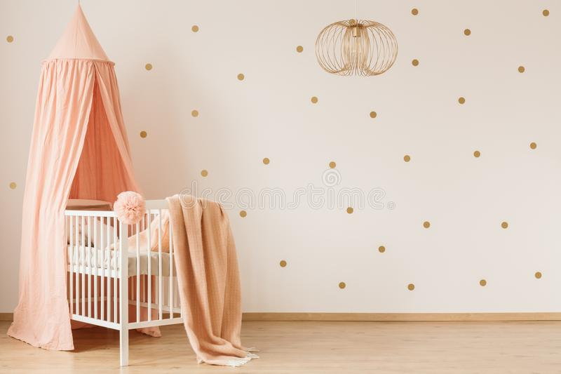 Blanket on crib. Dirty pink blanket thrown on white wooden crib with canopy in simple baby room interior with dotted wall stock photos