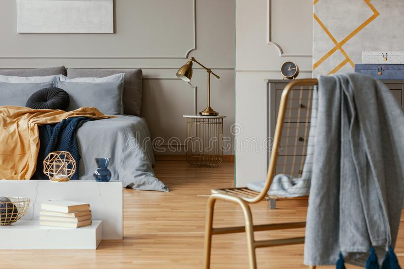 Blanket on golden chair in bright bedroom interior with grey wall. Blanket on golden chair in bright bedroom interior with wall royalty free stock photography