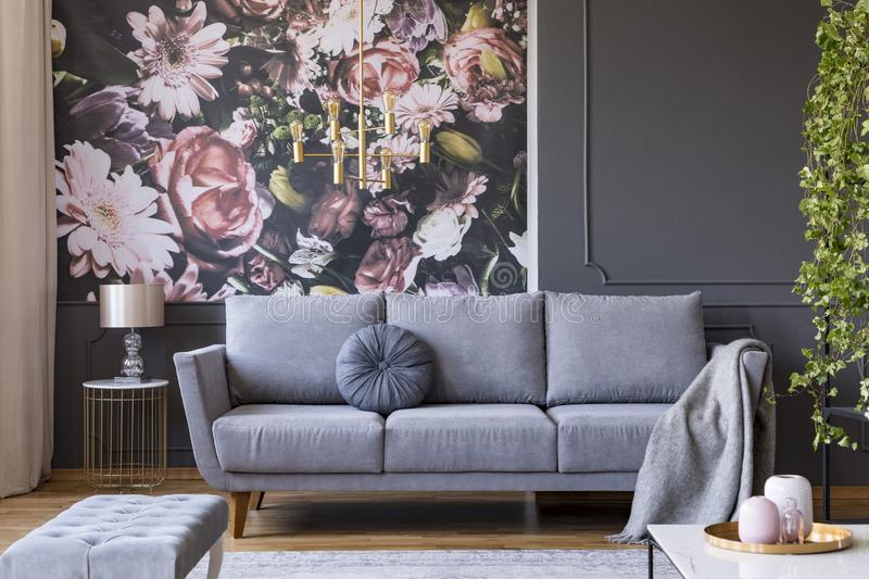 Blanket on grey couch in living room interior with flowers wallpaper and lamp on table. Real photo. Concept stock photos