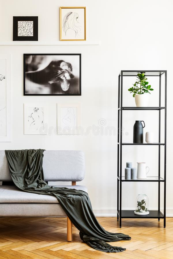 Blanket on grey sofa next to shelves in simple white living room interior with posters. Real photo stock photo