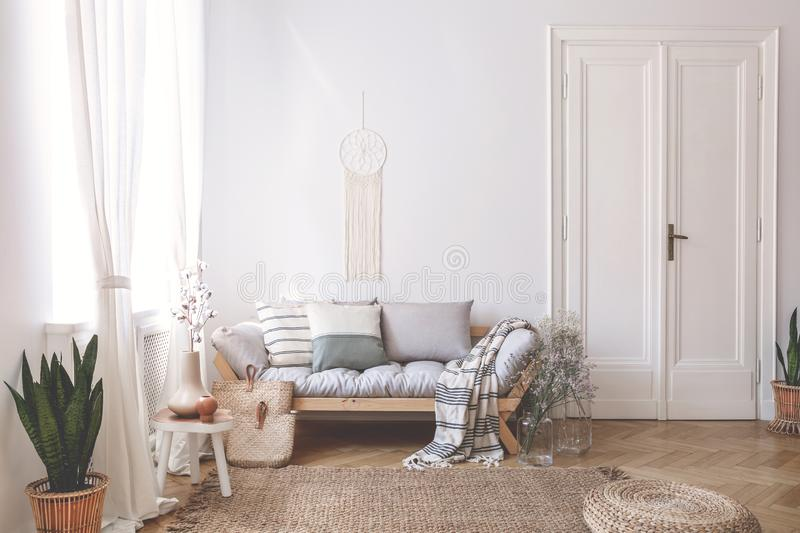 Blanket and pillows on wooden sofa in white loft interior with pouf and plant on carpet. Real photo. Concept royalty free stock images