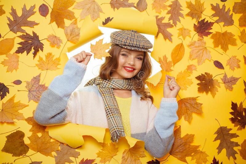 This blanket scarf has a lovely soft feel. Fashion girl look through torn paper with autumn leaves. Cute woman wear stock photography