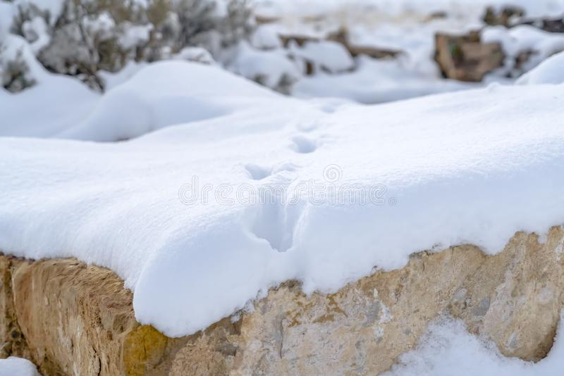 Blanket of snow on a rocky terrain with footprints. Close up view of a blanket of thick snow on a rocky terrain with footprints. Scenic snow covered landscape royalty free stock image