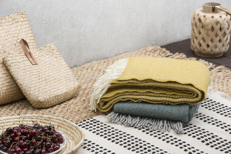 Blankets and rattan bags on table with cherries on the terrace of house. Real photo stock photo