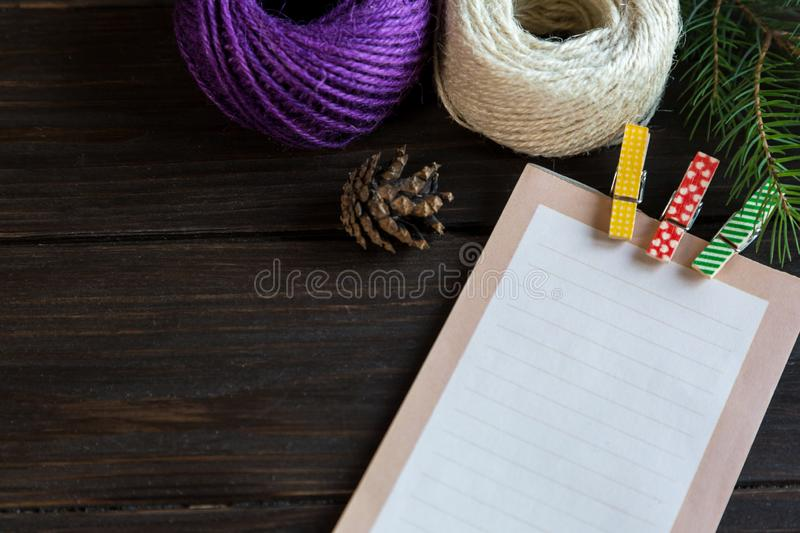 Blanknote lays on the wooden background to make a list of presents for friends and family. New year and Xmas preparation stock photos
