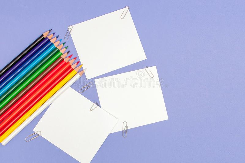 Blanks sheet of papers and color pencils on violet background for Projects and Announcements, copy space.  stock photos