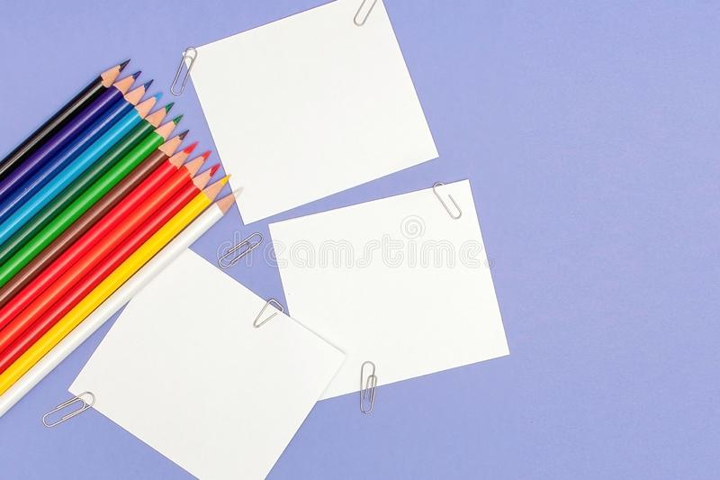 Blanks sheet of papers and color pencils on violet background for Projects and Announcements, copy space.  royalty free stock photos