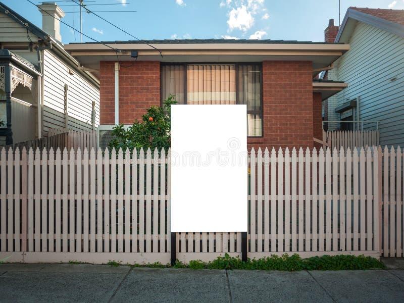 Blankt, vit mall för annonsering av fastighetsannonser, skylt/skylt/skylt framför ett typiskt bostadshus royaltyfri bild