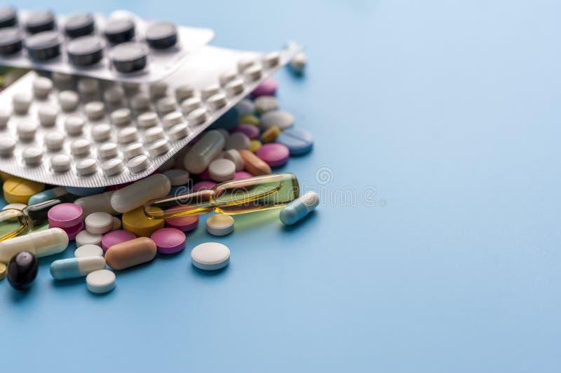 Blaren van pillen en verschillende capsules op blauwe achtergrond royalty-vrije stock afbeeldingen