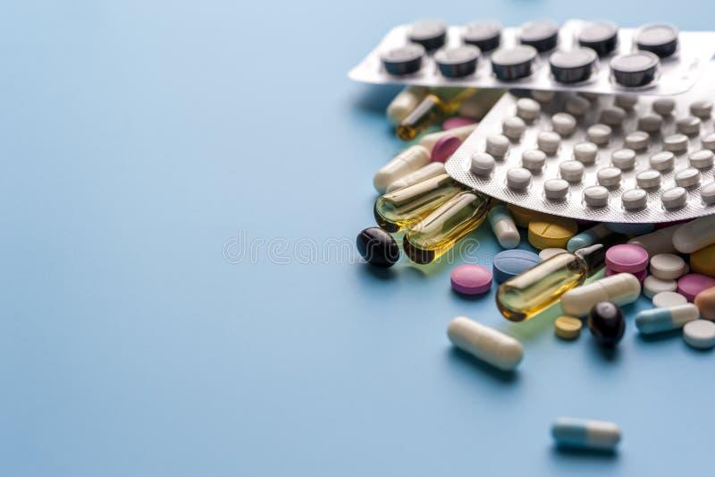 Blaren van pillen en verschillende capsules op blauwe achtergrond royalty-vrije stock foto