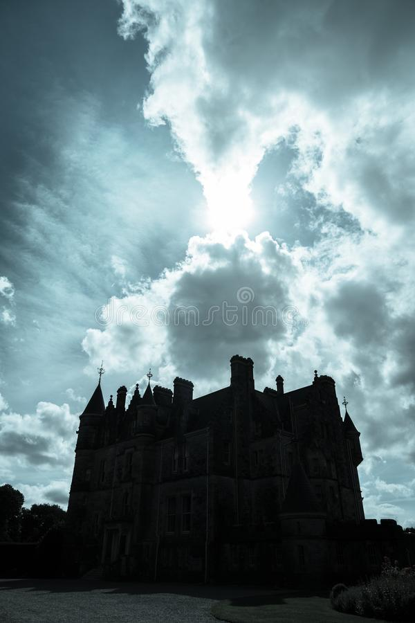 Dark silhouette scary looking medieval castle back-lit by sun royalty free stock images