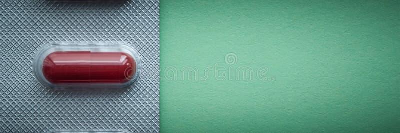 Blase mit dunkelroten Tabletten auf einem grünen Hintergrund stockbilder