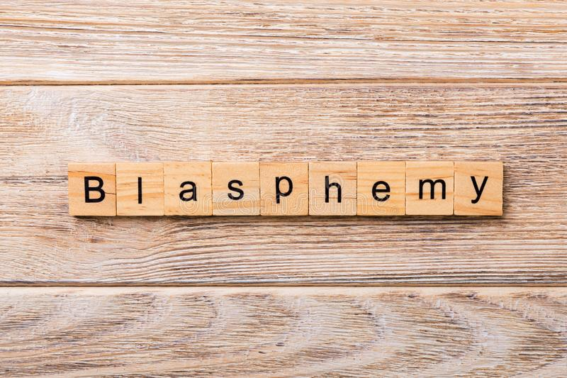 BLASPHEMY word written on wood block. BLASPHEMY text on wooden table for your desing, concept.  stock image