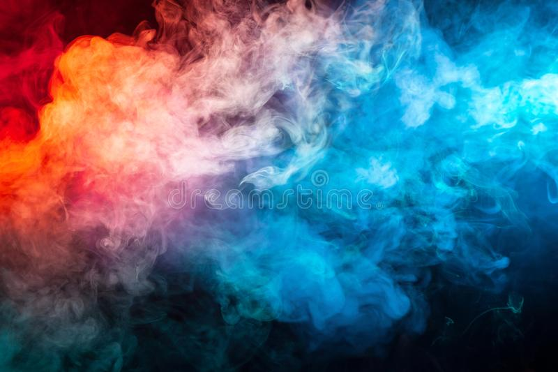 A blast of smoke evaporating in the colors of the rainbow: red, orange, yellow, green, cyan, magenta. Against a dark background stock photos