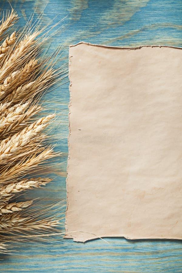 Blatt des Weizenähreweinlese-unbeschriebenen Papiers auf hölzernem Brett stockfoto