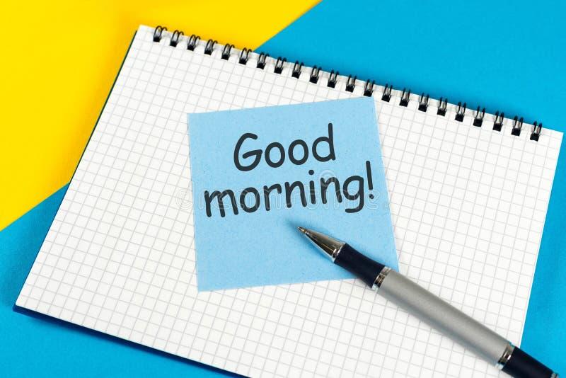 Blatt Papier mit gutem Morgen des Textes auf der gelb-blauen Tabellennahaufnahme lizenzfreie stockbilder