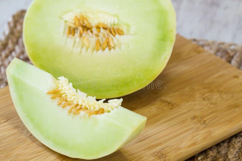 Blatthonig-Melonen-Scheibe auf hölzernem Schneidebrett lizenzfreie stockfotografie