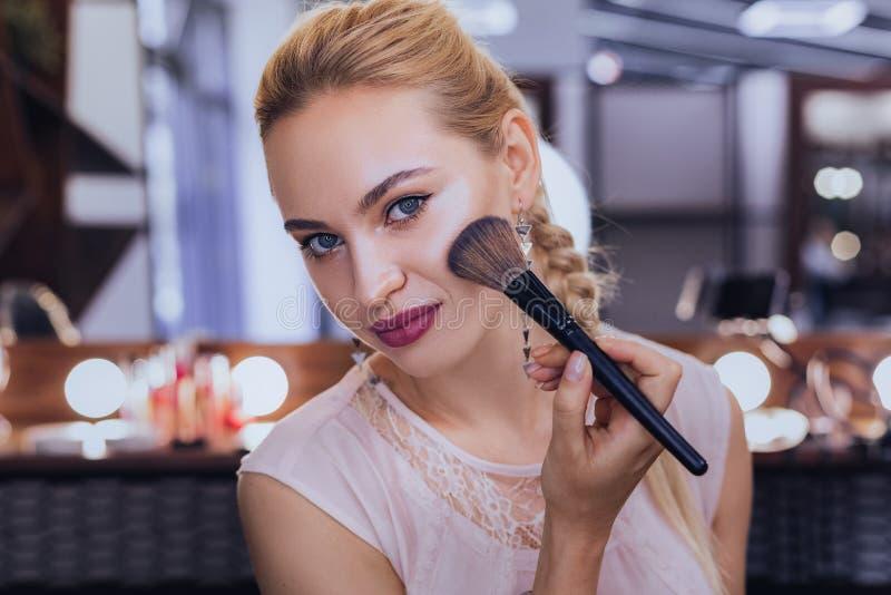 Blauäugige Frau, die Gesichtsbürste unter Verwendung des Pulverrouges hält lizenzfreies stockfoto