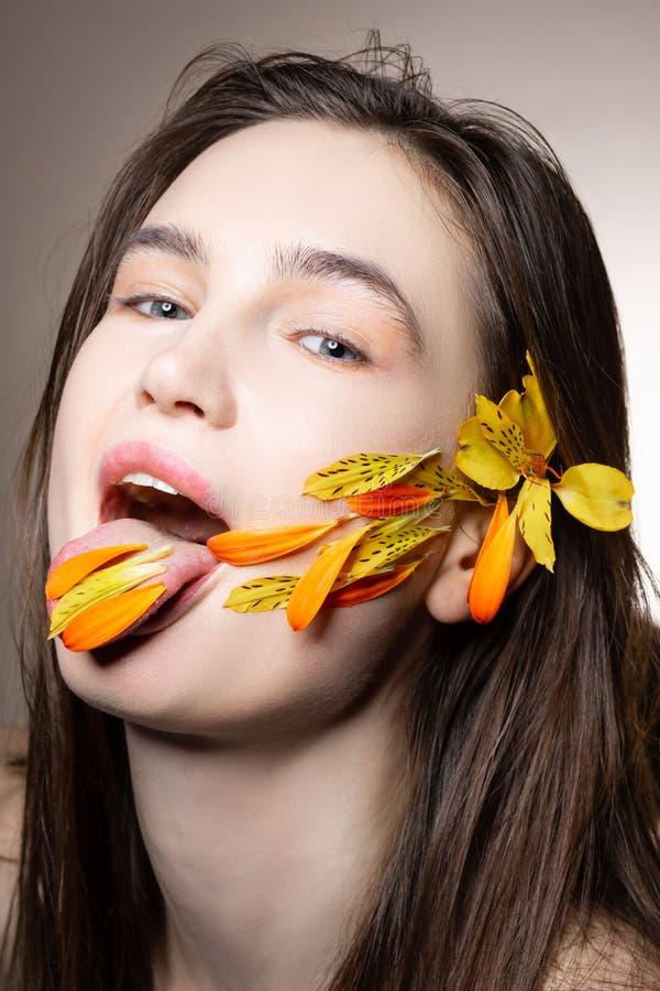 Blauäugiges aufwerfendes Modell beim Haben von Blumenblumenblättern auf ihrer Zunge stockfoto
