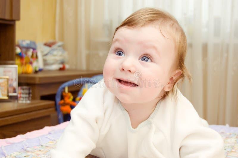Blauäugiges Baby, das auf Bett liegt lizenzfreies stockfoto