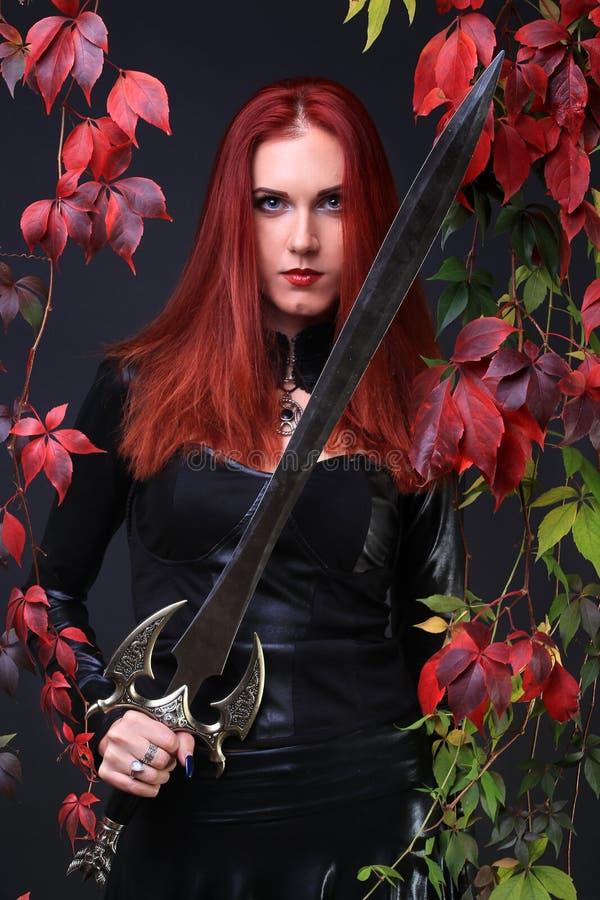 Blauäugiges rotes gotisches Hauptmädchen, das eine Fantasieklinge unter Herbstreben hält stockfotografie