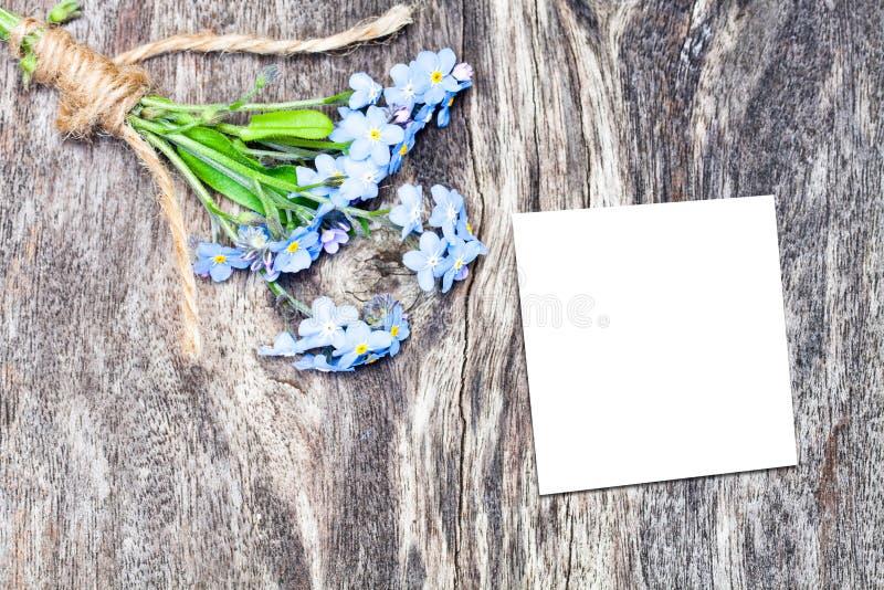 Blau blüht Blumenstrauß auf der Eichenbrauntabelle mit blauem Blatt Papier stockfotografie