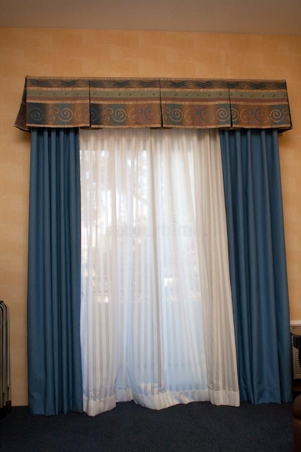 Blau drapiert Bedeckungfenster lizenzfreie stockfotos