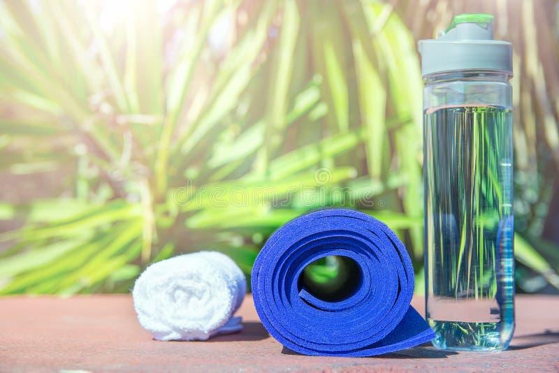 Blau gerolltes Yoga Mat Bottle mit Wasser-weißem Tuch auf Grün-Palme-Natur-Hintergrund Helles Mittagssonnenlicht Entspannung stockfoto