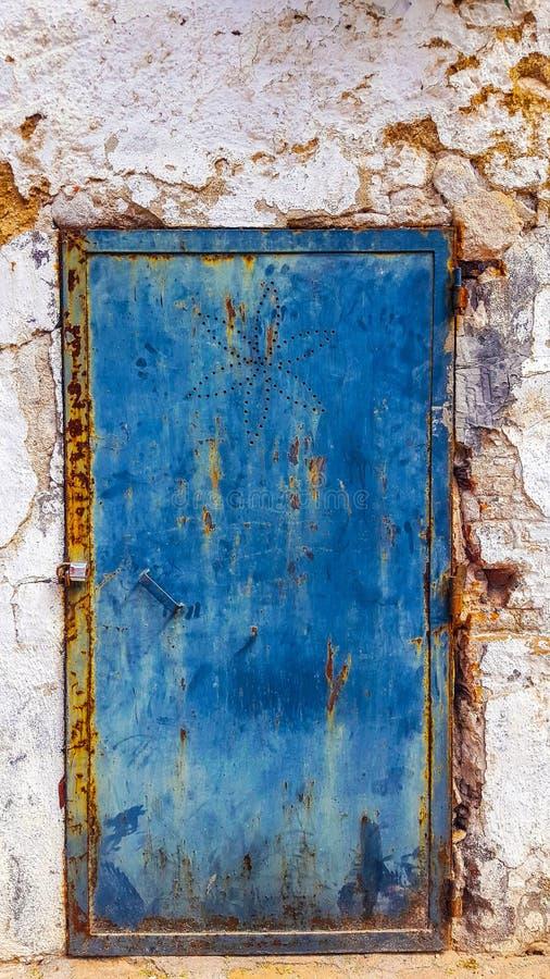 Blau malte Metalltür mit gebohrtem Blumenmuster Rostig, stai stockfotografie