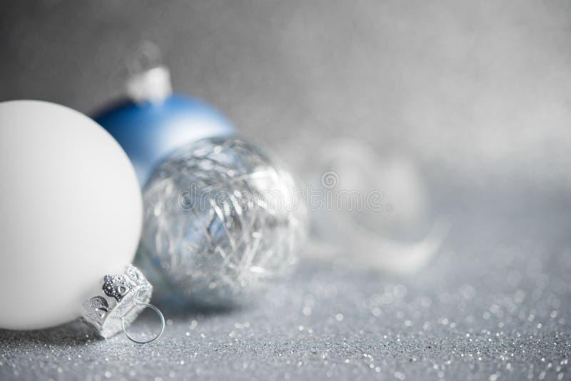 Blau, Silber und weiße Weihnachtsverzierungen auf Funkelnfeiertagshintergrund Frohe Weihnacht-Karte stockfotografie